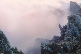 Craggy mountains frame a pink, misty sky and horizon