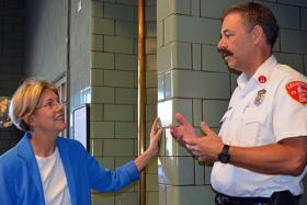 Elizabeth Warren speaks with a Lexington, Mass., firefighter on Sept. 10, 2012.