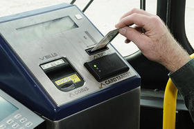 a person puts a charlie ticket into an mbta bus fare box