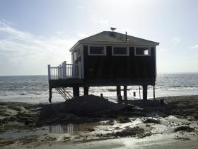 Storm surge and high surf washed right under this house on stilts on Falmouth's Surf Drive. Sand had to be cleared from the road by bulldozer.