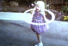 A little girl twirls a hula-hoop on a driveway.