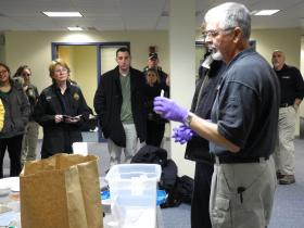 Author Patricia Cornwell and Cambridge Detective Dan Marshall look on as an instructor from the National Forensic Academy demonstrates crime scene management techniques