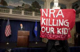 A protester holds up a sign as National Rifle Association executive vice president WayneLaPierre, left, speaks during a news conference in response to the Connecticut school shooting on Friday, Dec. 21, 2012 in Washington.