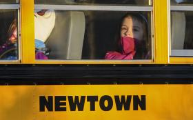 A girl sits on a Newtown bus leaving the new Sandy Hook Elementary School after the first day of classes in Monroe, Conn., Thursday, Jan. 3, 2013. The Sandy Hook students started today in a new school, formerly called Chalk Hill School in Monroe. It was r