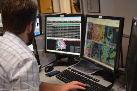 A man at the National Weather Service in Taunton observes storm data.