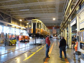 Orange line train in repair at the Wellington Station car shop.