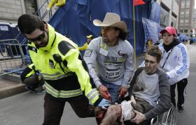 Jamaica Plain peace activist Carlos Arrendondo (in the cowboy hat) helped 27 y.o. Jeff Bauman Jr. as he was wheeled from the blast scene.