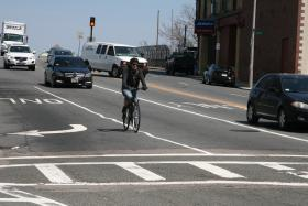 A biker shares the road with drivers in Allston.