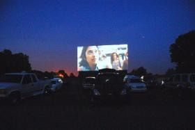 The sun sets as viewers take in a drive-in movie. Theaters are struggling to stay financially solvent as film studios begin the conversion to digital film.