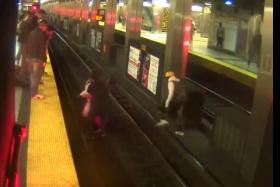 Three passengers rescue a fellow passenger who fell onto the tracks on the Orange Line. The man in the yellow hat (right) jumped over the third rail.