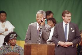 Nelson Mandela, deputy president of the African National Congress, wipes his brow in the hot, humid gymnasium of the Madison Park High School in the Roxbury section of Boston Saturday, June 23, 1990. An exhuberant crowd packed the gymnasium for Mandela's appearance.
