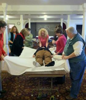 At an at-home funeral workshop in Westford, Mass., led by at-home funeral guide Peg Lorenz, participants practice wrapping and lifting a body for transport, demonstrated on a living person