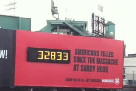 Developer John Rosenthal owns a parking garage in the shadow of Fenway Park. Rosenthal has featured billboards like this one to raise awareness of gun control.