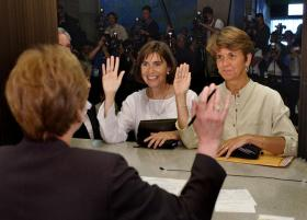 Hillary, right, and Julie Goodridge, left, lead plaintiffs in the Massachusetts gay marriage lawsuit, raise their right hands and affirm that everything on their marriage license is correct while at Boston City Hall in Boston in this Monday May 17, 2004 f