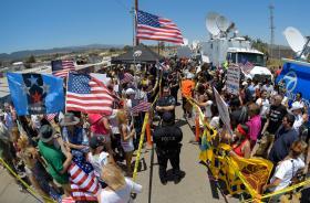 Demonstrators from opposing sides confront each other while being separated by Murrieta police officers, Friday, July 4, 2014, outside a U.S. Border Patrol station in Murrieta, Calif. Demonstrators on both sides of the immigration debate had gathered wher
