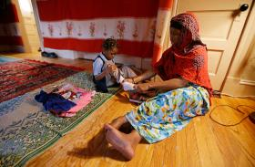 In this June 13, 2014 photo, Somali refugee Bollo Mohamed, 26, helps her daughter Malyun Mohamed, 5, with her shoes while dressing her for preschool at their apartment in Springfield, Mass. Bollo lived in a Kenyan refugee camp from 1992 until 2007 when sh