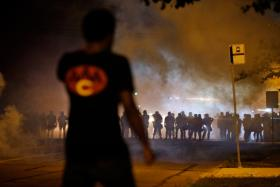 In this Aug. 13, 2014 file photo, a man watches as police walk through a cloud of smoke during a clash with protesters in Ferguson, Mo.