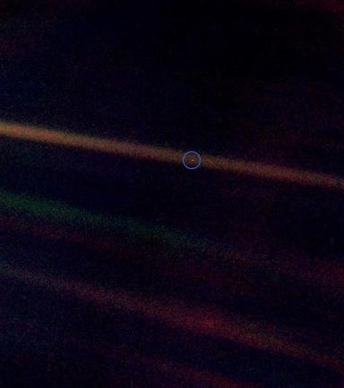 "Earth. Seen in 1990 as a ""pale blue dot"" from Voyager 1, about 6 billion kilometers (3.7 billion miles) away"