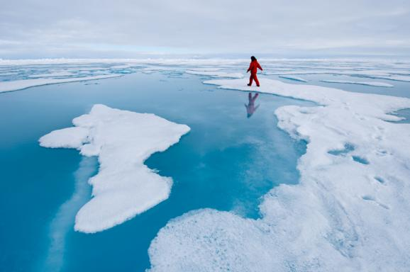 A graduate student takes samples from a melt pond in hopes of discovering new species of Arctic microbes.