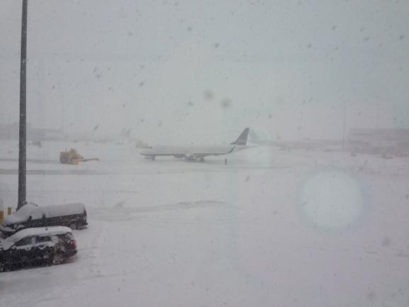 A plow and a plane are battered by snow at Logan Airport.