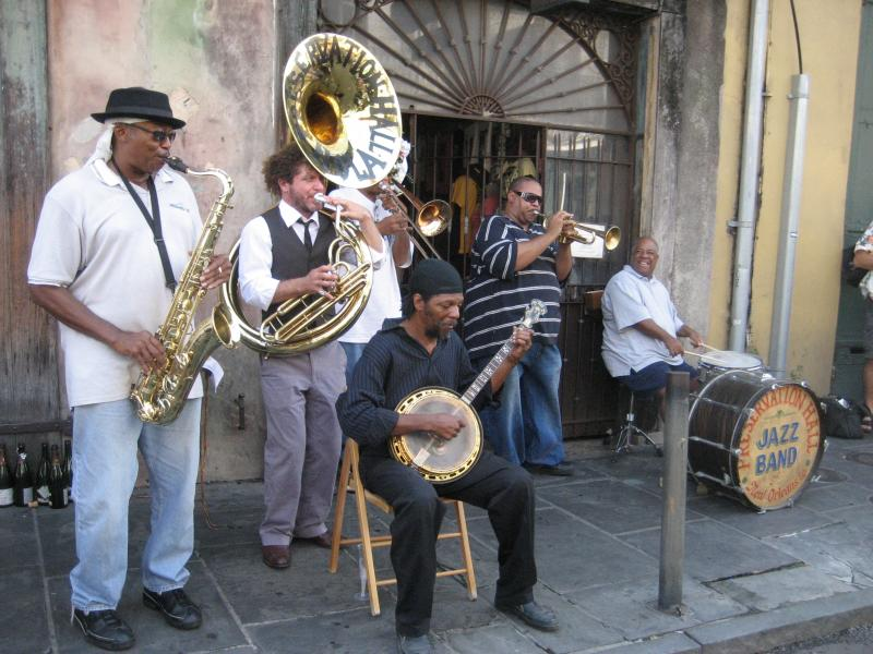 Preservation Hall Jazz band plays on sidewalk in front of the Hall in New Orleans. Ben Jaffe, sousaphone; Carl Le Blanc, banjo; Joe Lastie, drums. Photo courtesy of Infrogmation