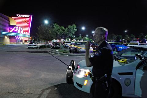 An Aurora, Colo., police officer talks on his walkie-talkie after the shooting.
