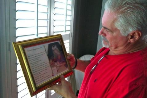 Steve Davis holding a picture of his late sister, Debbie.
