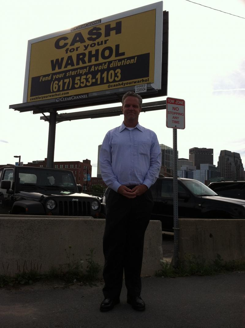 The artist, Geoff Hargadon, standing with the Cash for your Warhol billboard.
