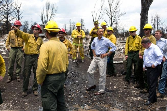President Obama surveys damage from this summer's wildfires in Colorado. Some experts say global warming could result in greater numbers of wildfires.