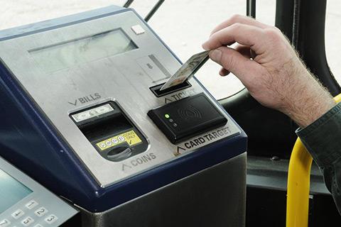 a person puts a charlie ticket into an mbta bus fare box