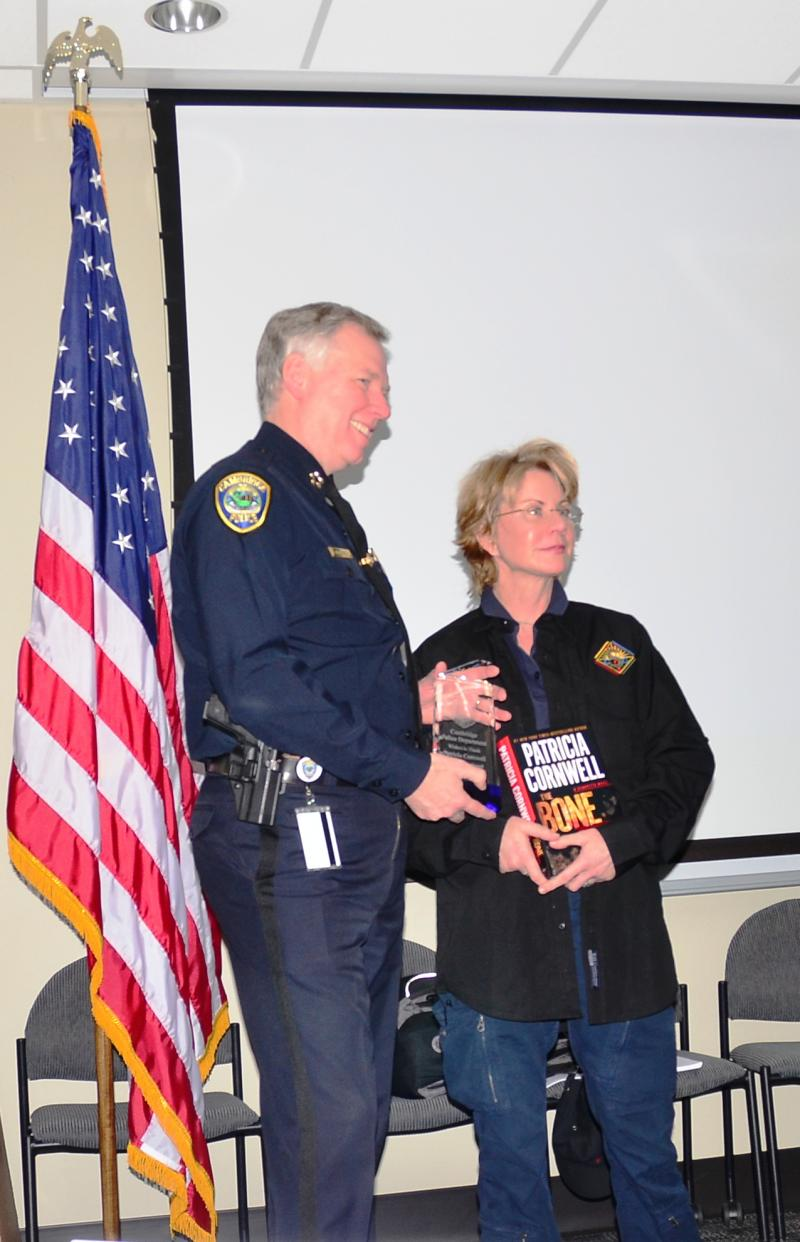 Cambridge Police Commissioner Robert Haas presents author Patricia Cornwell with a crystal plaque