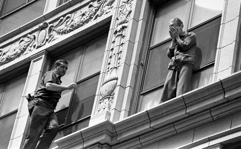 A fireman rescues an elderly woman from a suicide attempt on Chauncy St. in Chinatown.