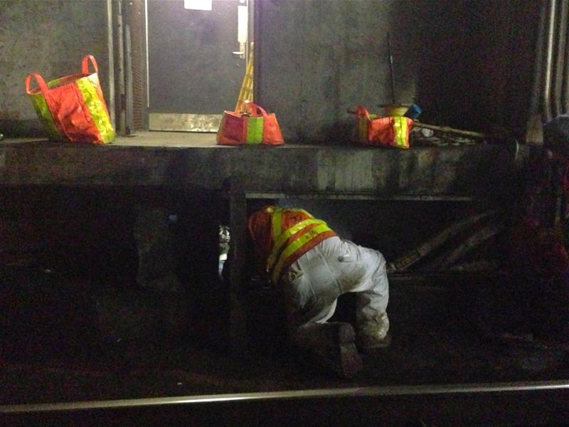 A T employee climbs into a manhole.