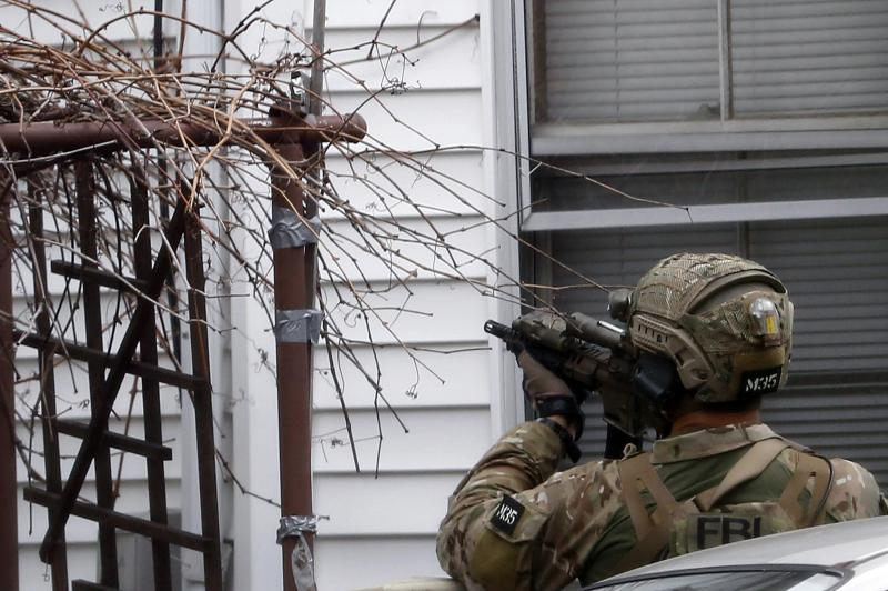 A FBI agent points a weapon at the house next to 412 Norfolk Street in Cambridge, Massachusetts April 19, 2013. Police killed one suspect in the Boston Marathon bombing, Tamerlan Tsarneav, in a shootout and mounted house-to-house searches for the second m