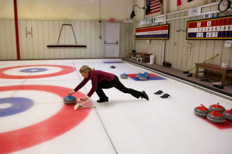 A member of the Cape Cod Curling Club uses a balancer to stay upright as she throws a stone.