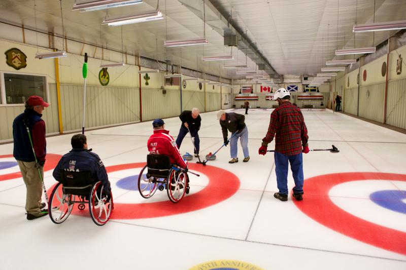 Paralympians Meghan Lino and David Palmer curling with members of the Cape Cod Curling Club.