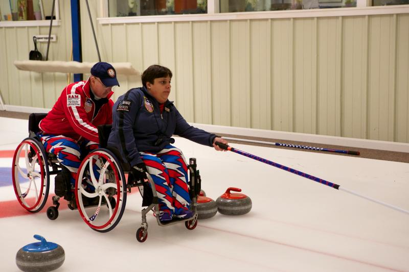Meghan throws a stone. Wheelchair curlers line up tandem for stability when throwing stones.