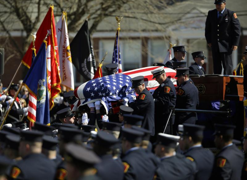 The casket containing the body of Boston firefighter Michael R. Kennedy is carried off his fire truck before his funeral outside Holy Name Church in Boston, Thursday, April 3, 2014. ennedy and Boston Fire Lt. Edward J. Walsh were killed March 26.