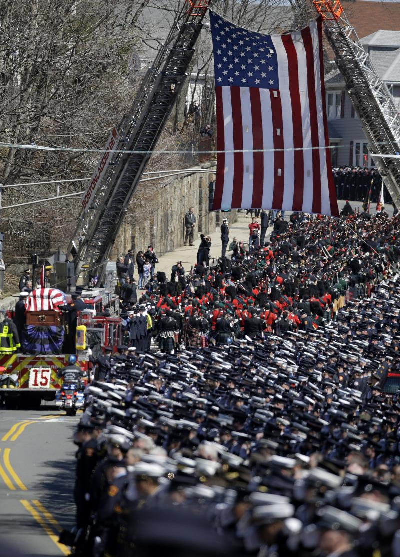 A fire truck carrying the casket of Boston firefighter Michael R. Kennedy leaves Holy Name Church in Boston, en route to the cemetery after Kennedy's funeral Thursday, April 3, 2014.