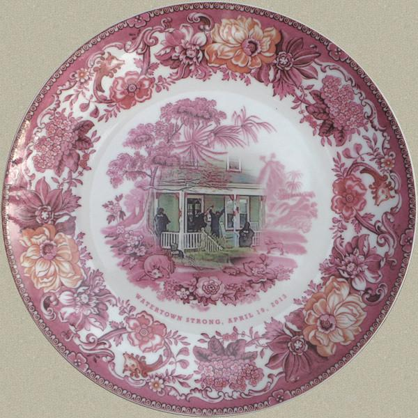 """The """"rose"""" plate shows a Watertown resident with his hands up being ordered our of his home. The plates were part of a limited-edition sale that ended in January."""