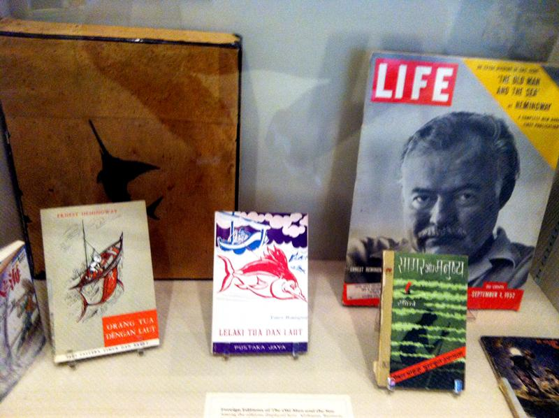 Copies of The Old Man and the Sea in multiple languages, and a LIFE magazine with Hemingway on the cover.