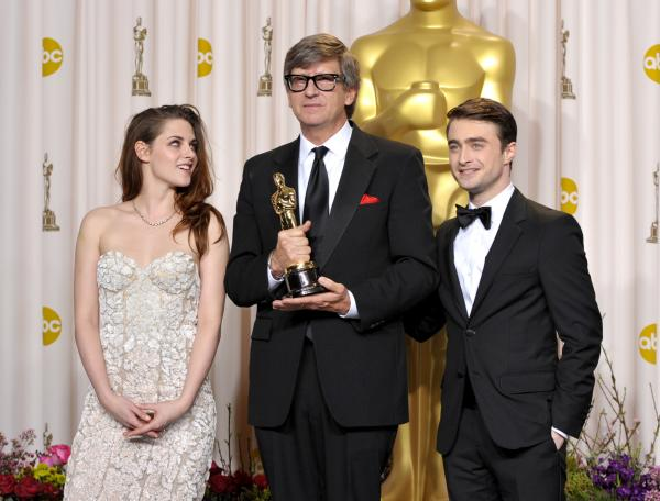 Presenter Kristen Stewart, left, Rick Carter with his award for best production design for Lincoln, and Daniel Radcliffe pose during the Oscars.