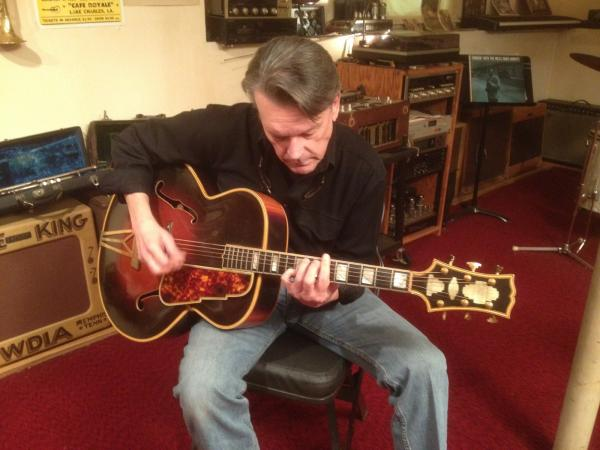 Musician J. Geils playing guitar in his home.