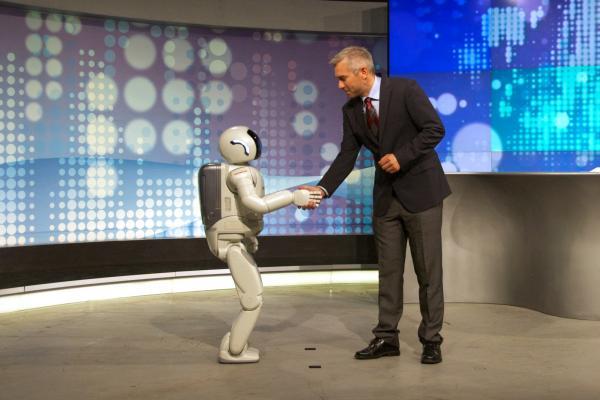 Asimo, a humanoid robot, shakes hands.