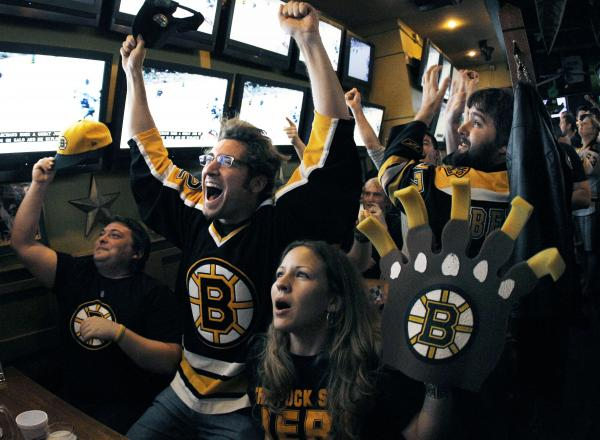 Boston Bruins fans react at the Boston Sports Grille near TD Garden in Boston on Wednesday, June 15, 2011, after the Bruins scored in the first period of Game 7 of the NHL hockey Stanley Cup Finals against the Vancouver Canucks in Vancouver, British Colum