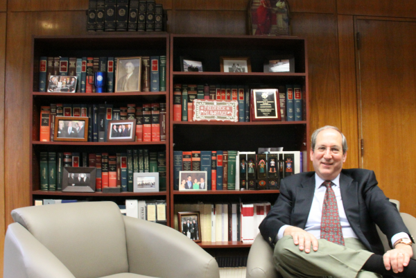 Brandeis University President Frederick Lawrence sits in his office beneath a photo of Supreme Court Justice Louis Brandeis.