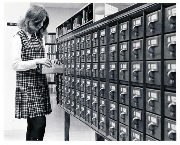 A woman using a card catalog.