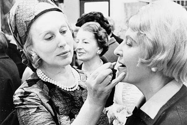 Estee Lauder helps a customer apply lipstick in 1966.