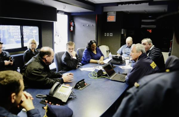 In this April 19, 2013 Massachusetts State Police photo, federal, state and local law enforcement officials discuss their strategy during the search for 19-year-old Boston Marathon bombing suspect Dzhokhar Tsarnaev at at mobile command center set up near
