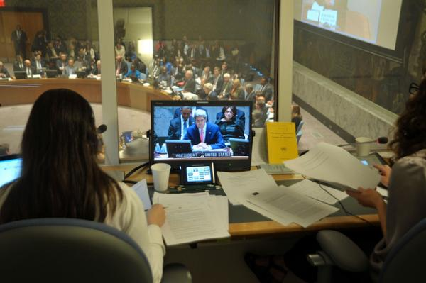 Translators at the United Nation watch a video of Secretary of State John Kerry.